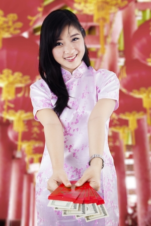 Happy beautiful girl holding money in red envelopes on Chinese New Year photo