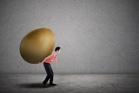 Businessman is carrying a big golden egg on grey background Stock Photo - 25360004