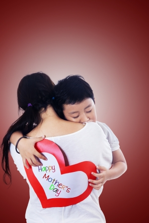 Boy hug mother holding love card on red photo
