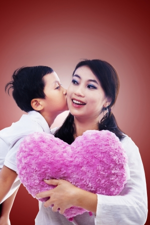 Boy kiss mother holding heart pillow on red background photo