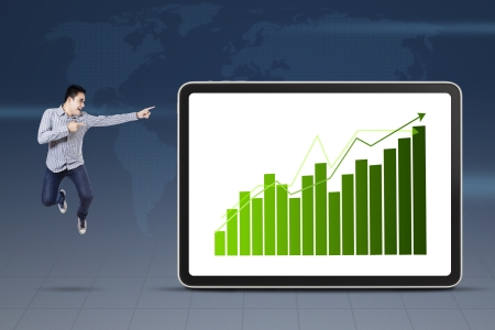 Young businessman jumping and pointing at growth graph photo