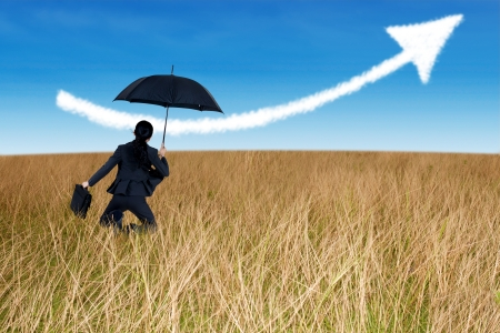 Businesswoman jumping to blue sky in grassland with umbrella photo