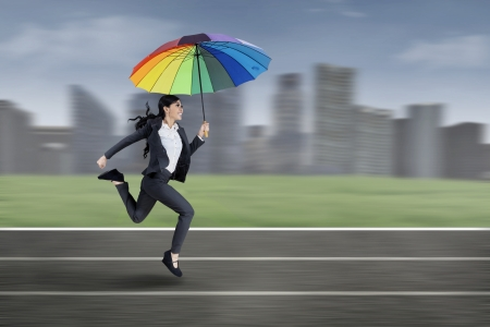 Excited businesswoman running with colorful umbrella on a running track photo