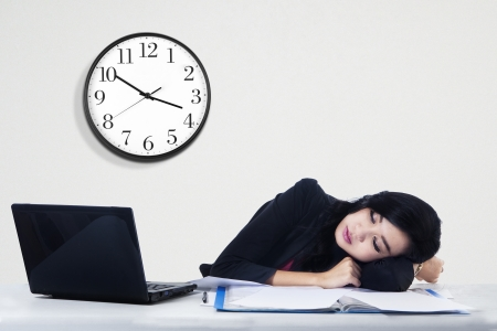 Tired beautiful business woman sleeping on her desk in office photo