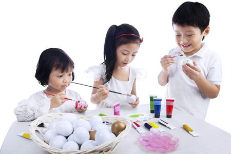 Drie kinderen schilderen paaseieren geïsoleerd op een witte achtergrond Stockfoto