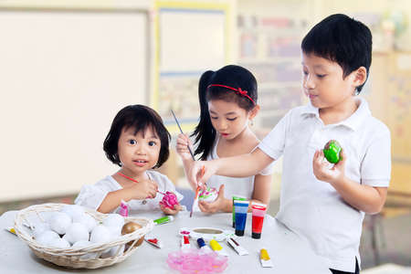 Group of children are painting easter eggs photo