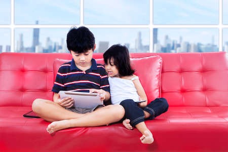 Children using tablet together sitting on the couch photo