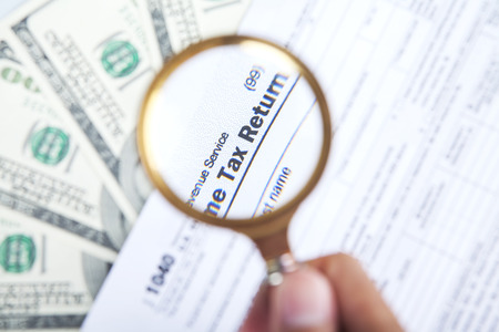 financial audit: Tax audit concept with a magnifying glasses, tax form, and money Stock Photo