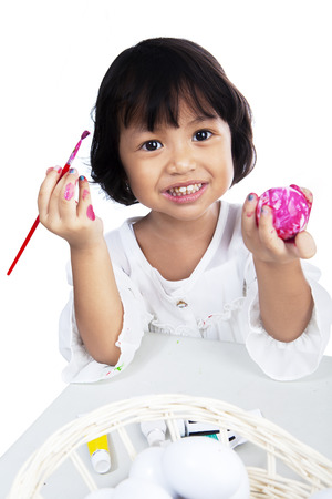 Cute little girl is coloring an easter egg with paintbrush photo