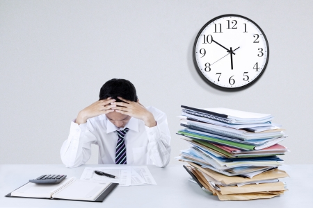 Depressieve jonge zakenman die zijn hoofd op het kantoor van