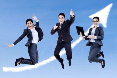 Gruppe von Geschäftsleuten Springen mit Notebook auf dem Himmel