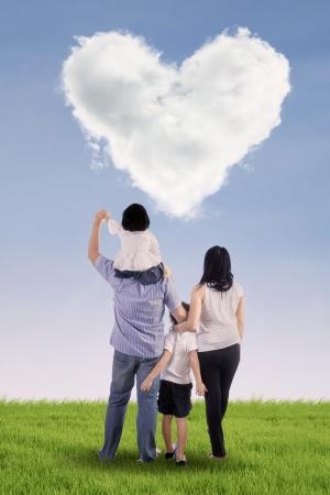 Familia que mira las nubes en forma de corazón en el campo verde Foto de archivo