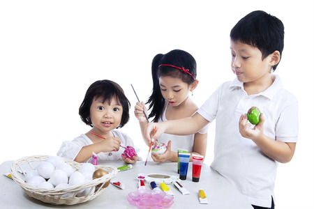 Three happy children painting easter eggs isolated on white background photo