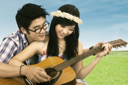 Portrait of happy couple playing guitar at the park photo