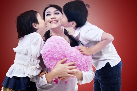 Happy mom kissed by children on red background photo