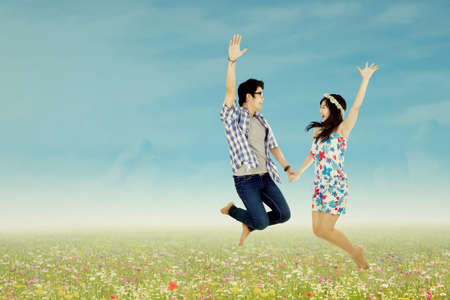 Happy young couple jumping in the field photo