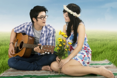 A romantic man playing guitar for his girlfriend shooting outdoors photo