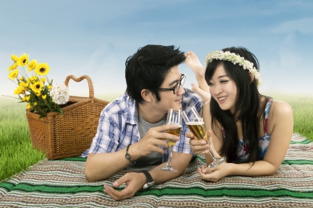 korean man: Young couple having a wine toast at a picnic