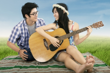 Romantic couple playing guitar together shooting outdoors photo