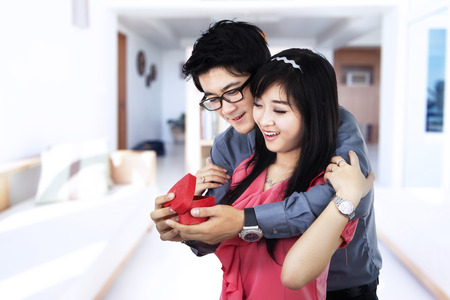 A romantic young couple with gift at home photo