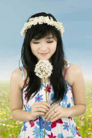 Beautiful woman with crown of flower is smelling flower photo