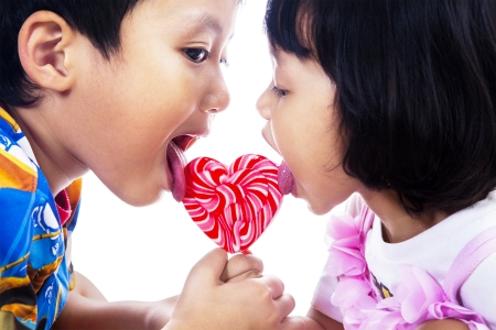 girl licking: Happy brother and sister lick a lollipop isolated on white background  Stock Photo