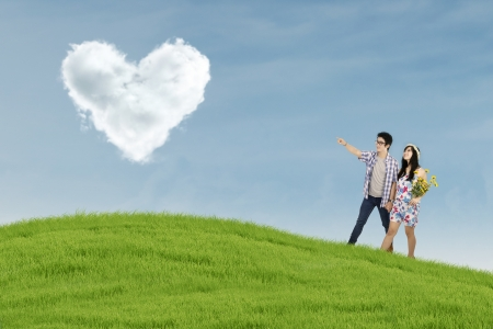 Romantic young couple looking at heart shaped clouds on the field photo