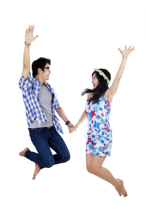 happy asian couple: Young couple holding hands and jumping - isolated on white background