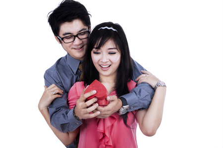 filipino adult:  Young man giving a gift to his girlfriend on valentines day
