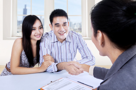 Asian couple hand shake with businesswoman at office