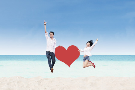 Asian couple jumping with heart card at the beach photo