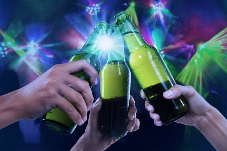 Closeup of hands toasting with bottles of beer at the party club Stock Photo