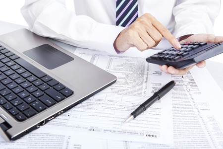 Closeup of hands counting taxes using calculator Stock Photo