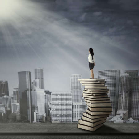 Young businesswoman looking at future and standing on a pile of books photo