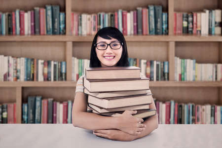 Young asian college student with books in library photo