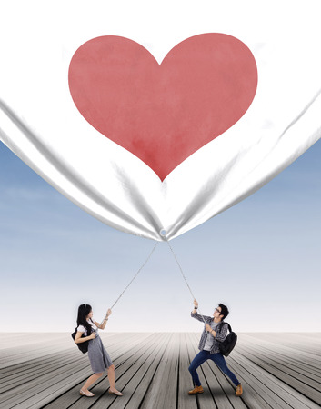 A young couple pulling big banner with heart symbol photo