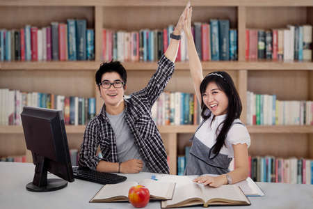 highschool students: Happy young student couple in the library Stock Photo