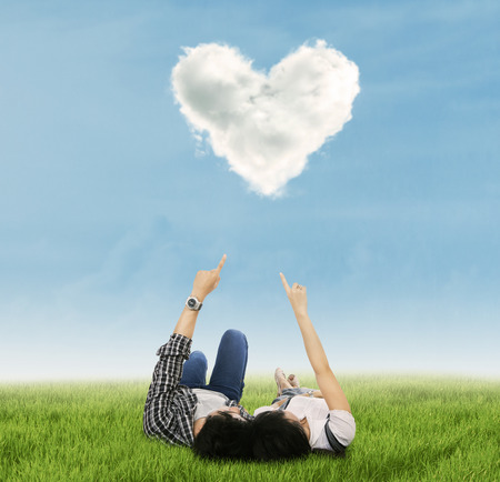 under heart: Couple enjoy holiday under heart cloud in park