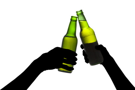 gripping bars: Silhouette of hands toasting with bottles of beer Stock Photo