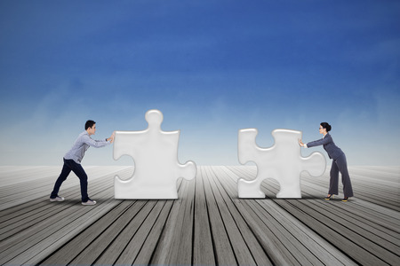 Two business people are working together to put two puzzles photo
