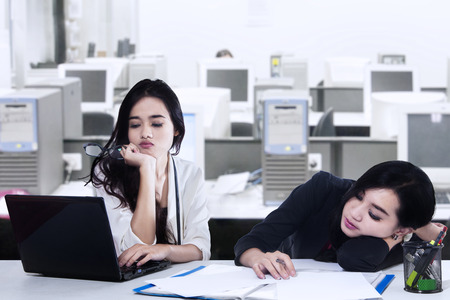 Two businesswoman exhausted with a laptop on the desk in office photo