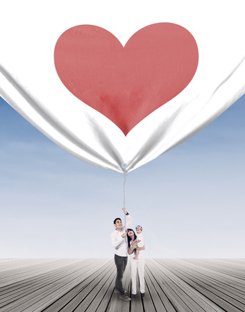 indian happy family: A happy family pulling big banner with heart symbol Stock Photo
