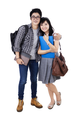 Happy trendy college students with bags and books, posing together, smiling at camera, photo