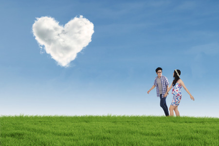 Romantic young couple walking together on the meadow while holding hands with heart shaped cloud photo
