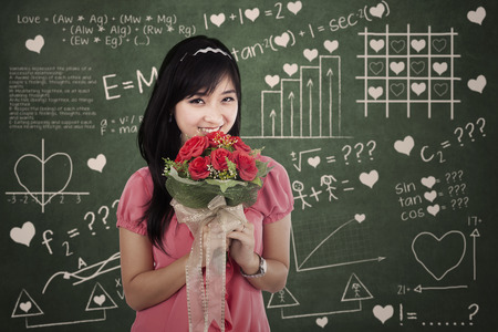 Woman with flowers standing in front of the formula of love photo