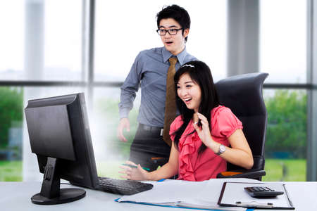 Young business couple shocked in front of computer on the desk photo