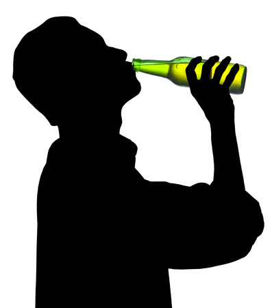 Silhouette of drunk man drinking a bottle of beer photo