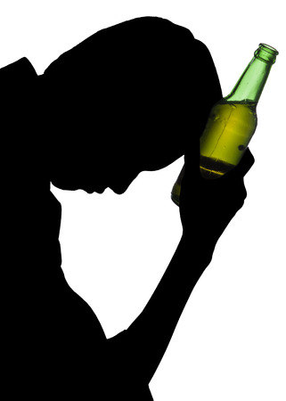 Silhouette of drunk man holding a bottle of beer  photo