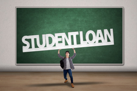 Young male college student holding a sign of student loan photo