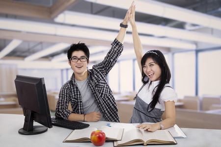 Successful young student couple in the classroom photo